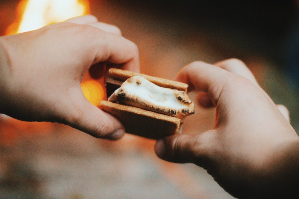 White man holding a s'mores dessert in-between his two hands with a fire burning in the background. Outdoor shot.