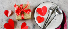 valentine's day decor including red paper hearts, cutlery, and a neatly wrapped gift. Romantic table setting.