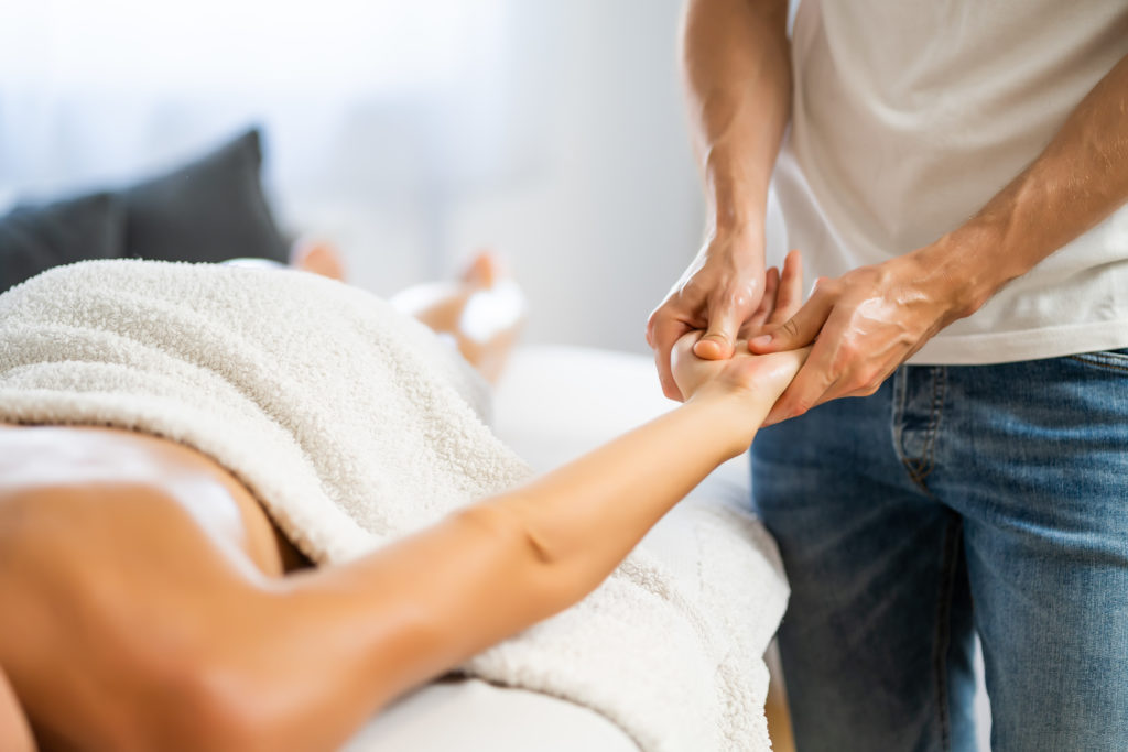 A female laying naked under a white towel getting a massage from a male wearing denim blue jeans and a white shirt.