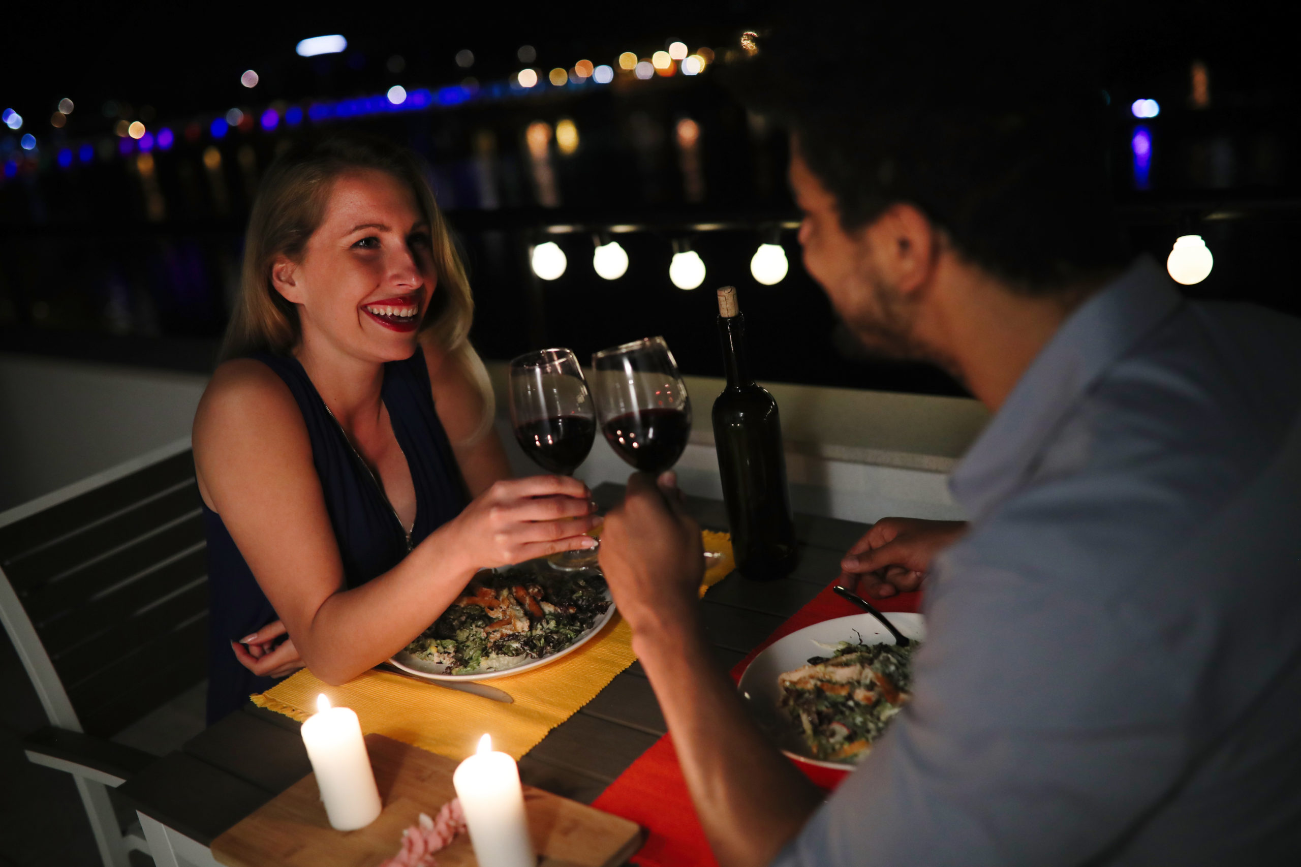 Young beautiful couple in love having romantic dinner at night on rooftop