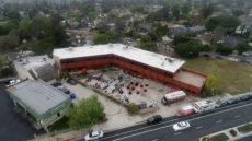 Overhead photograph of JohnHart Campus, owned by JohnHart Real Estate in La Crescenta-Montrose. Red building, two stories with a white roof.