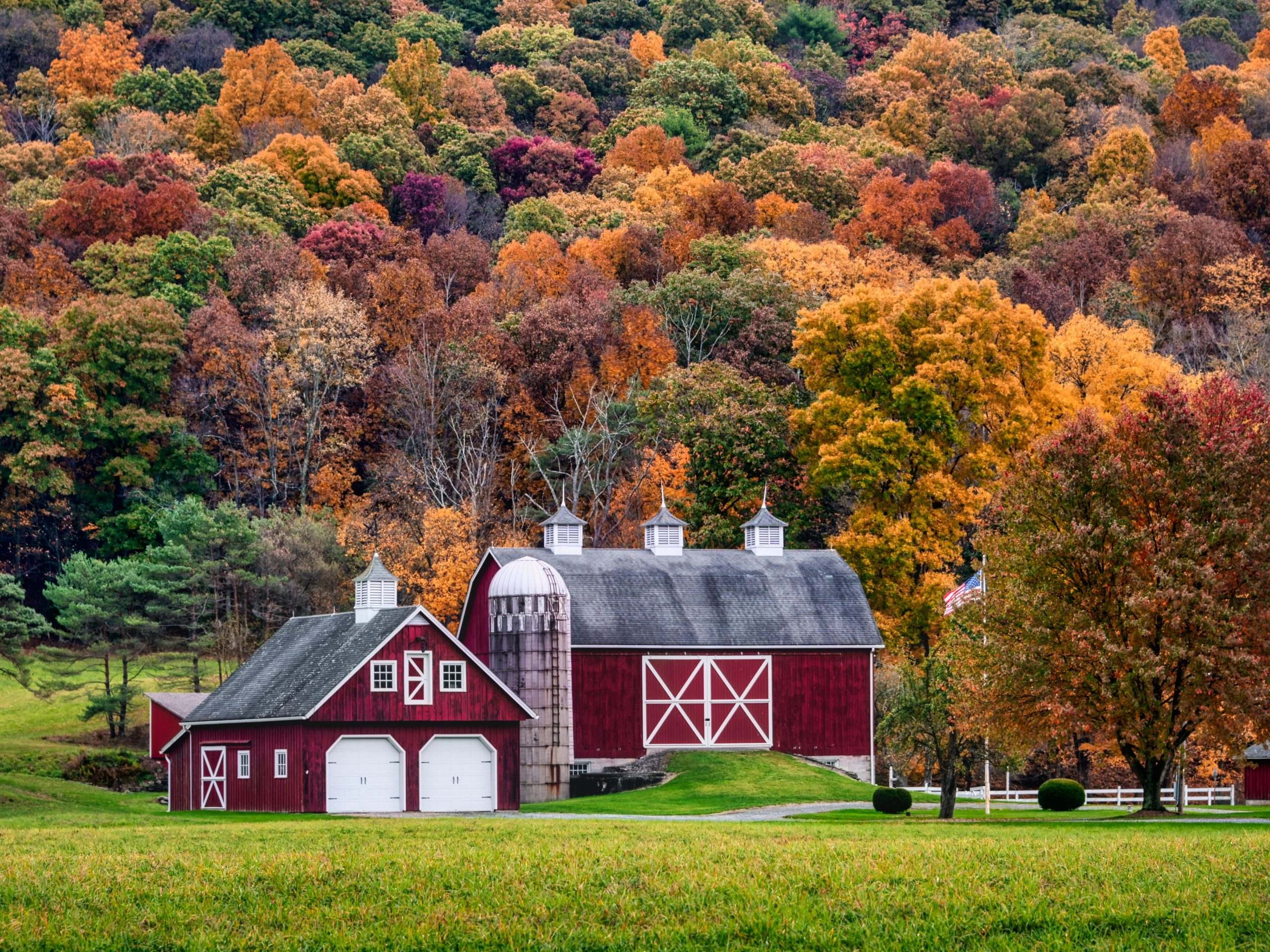 Red traditional barn house surrounded by orange and red trees in The Poconos