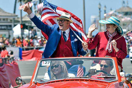 Happy waving man and woman in patriotic clothing holding American flags, sitting in a convertible in a parade.