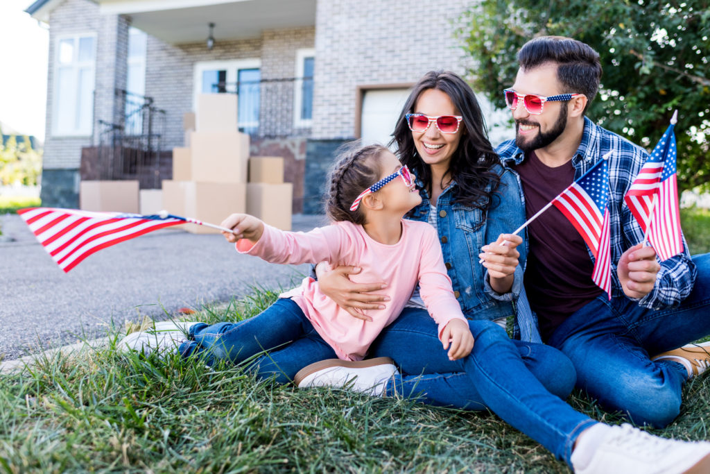 Family with Ameruican flags and sunglasses sitting on the lawn of their new house with boxes behind them