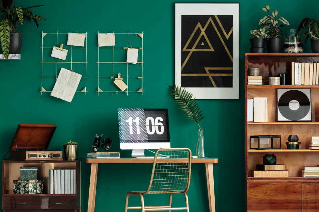Green home office interior with a computer on the desk, wooden cabinet and poster on the wall