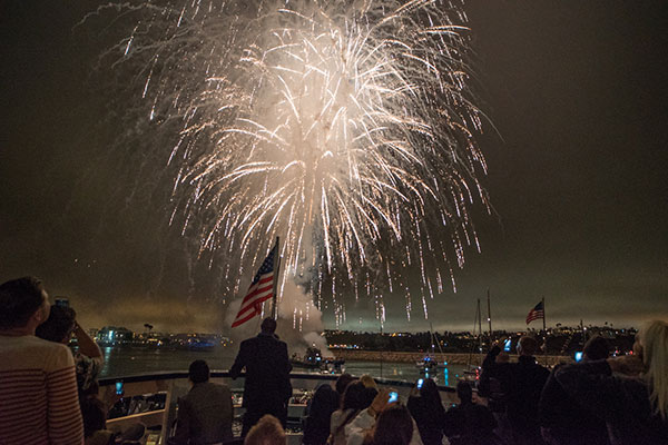 Fireworks in the Marina Del Rey bay with onlookers in a boat with an American flag