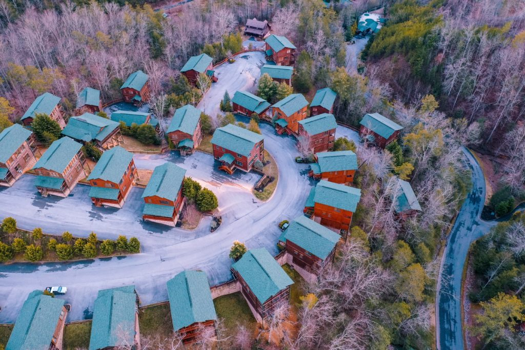 Aerial view of cabin-lined street in the woods near a stream in Gatlinburg, Tennessee