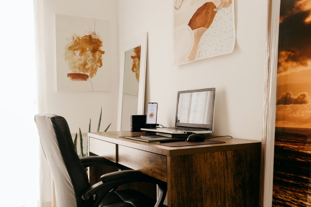 Modern home office with brown desk, black chair, black laptop, and brown watercolor paintings on the walls