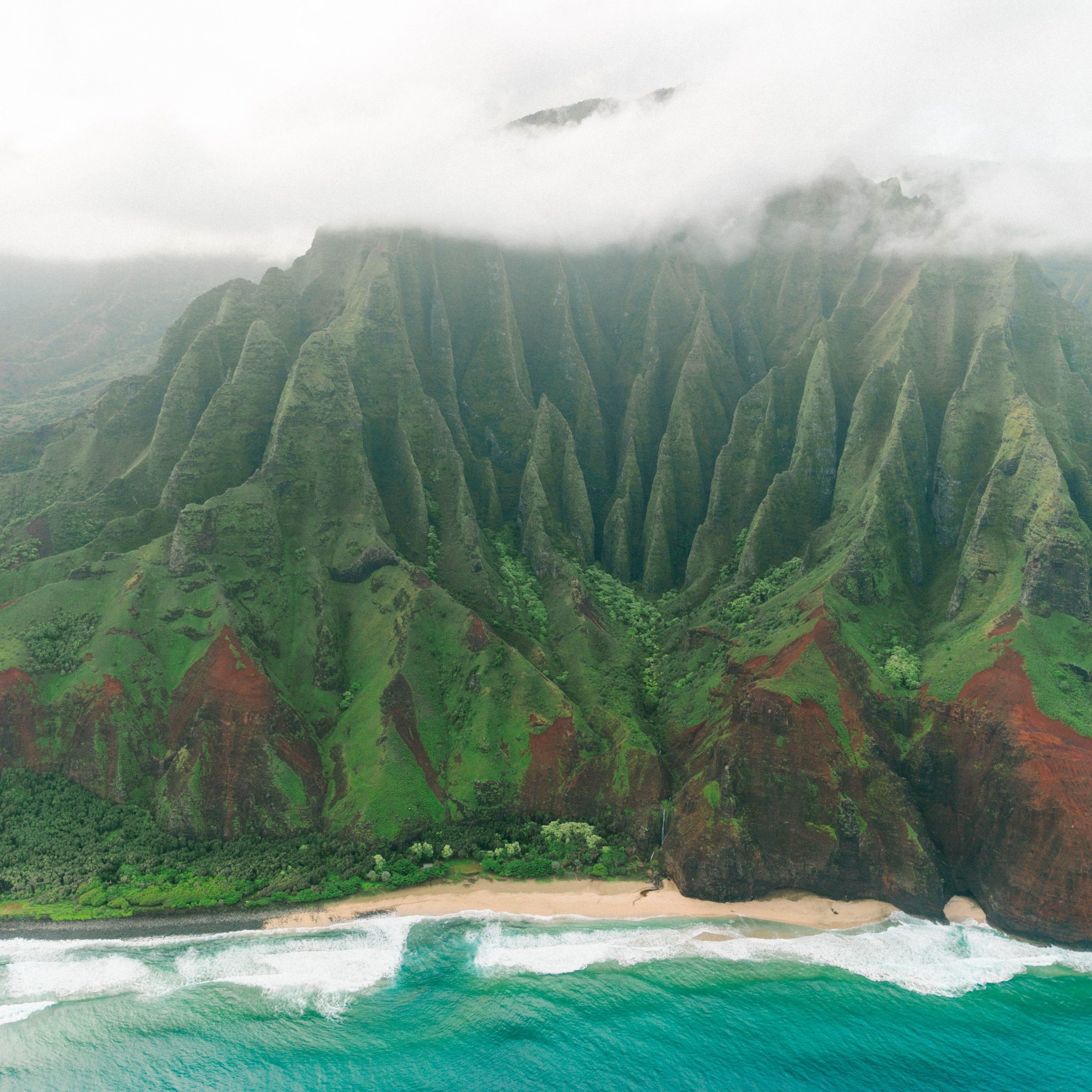 Green cliffs with misty clouds on the beach in Kauai with bright blue ocean water below