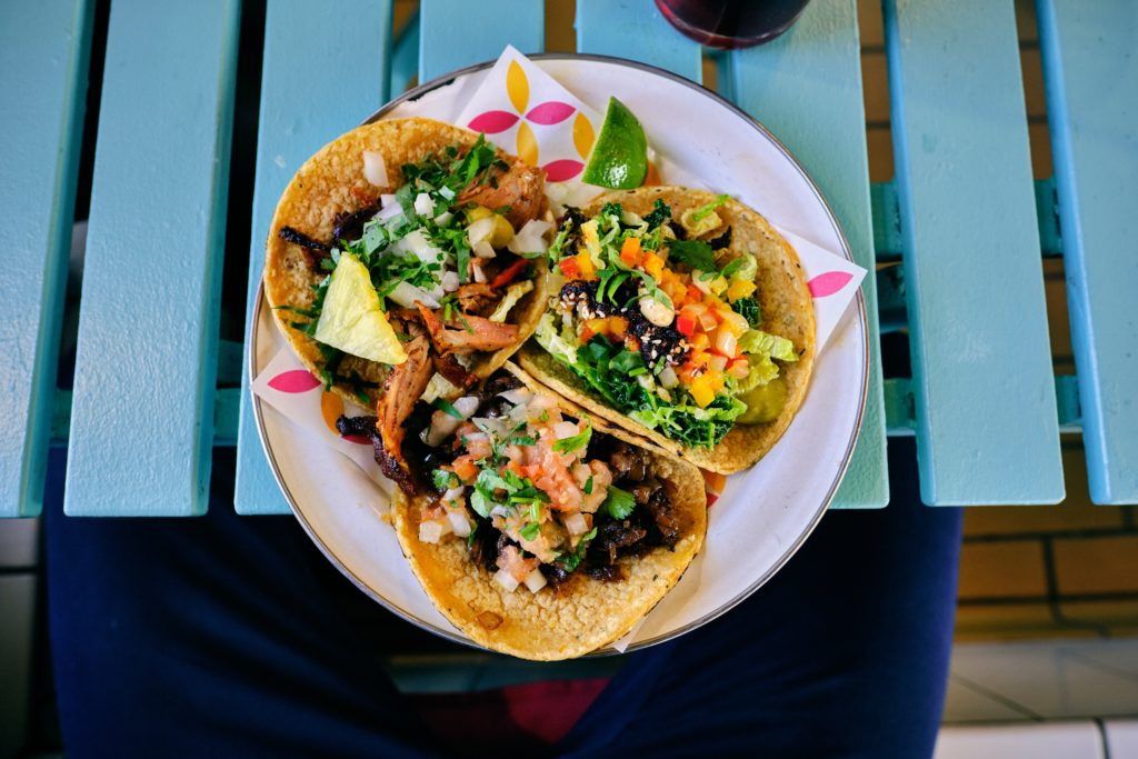 Three street tacos with lots of toppings laid on a plate on a bright blue picnic table.