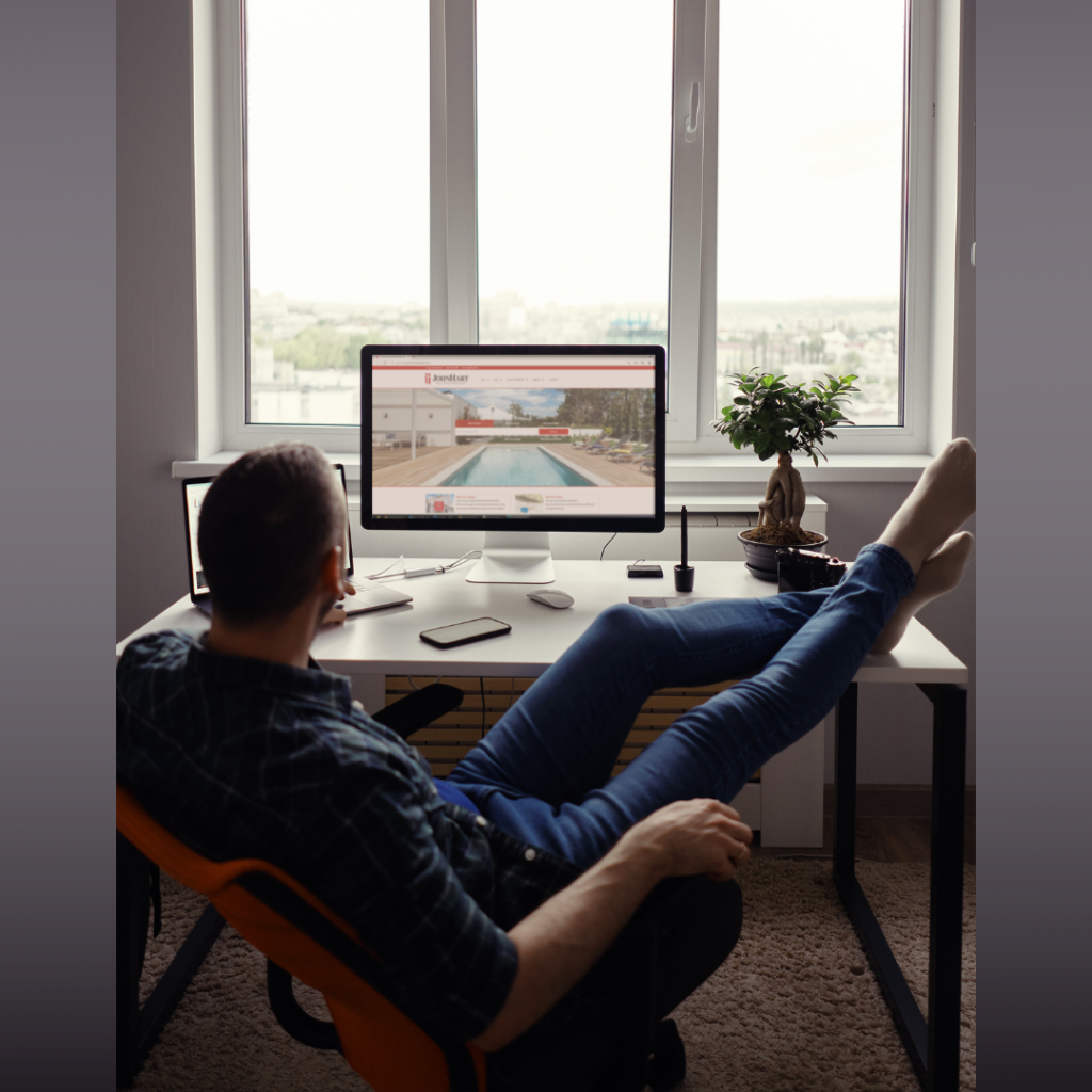 Man relaxes with his feet up on his desk sitting in front of a sunny window while looking at his computer monitor