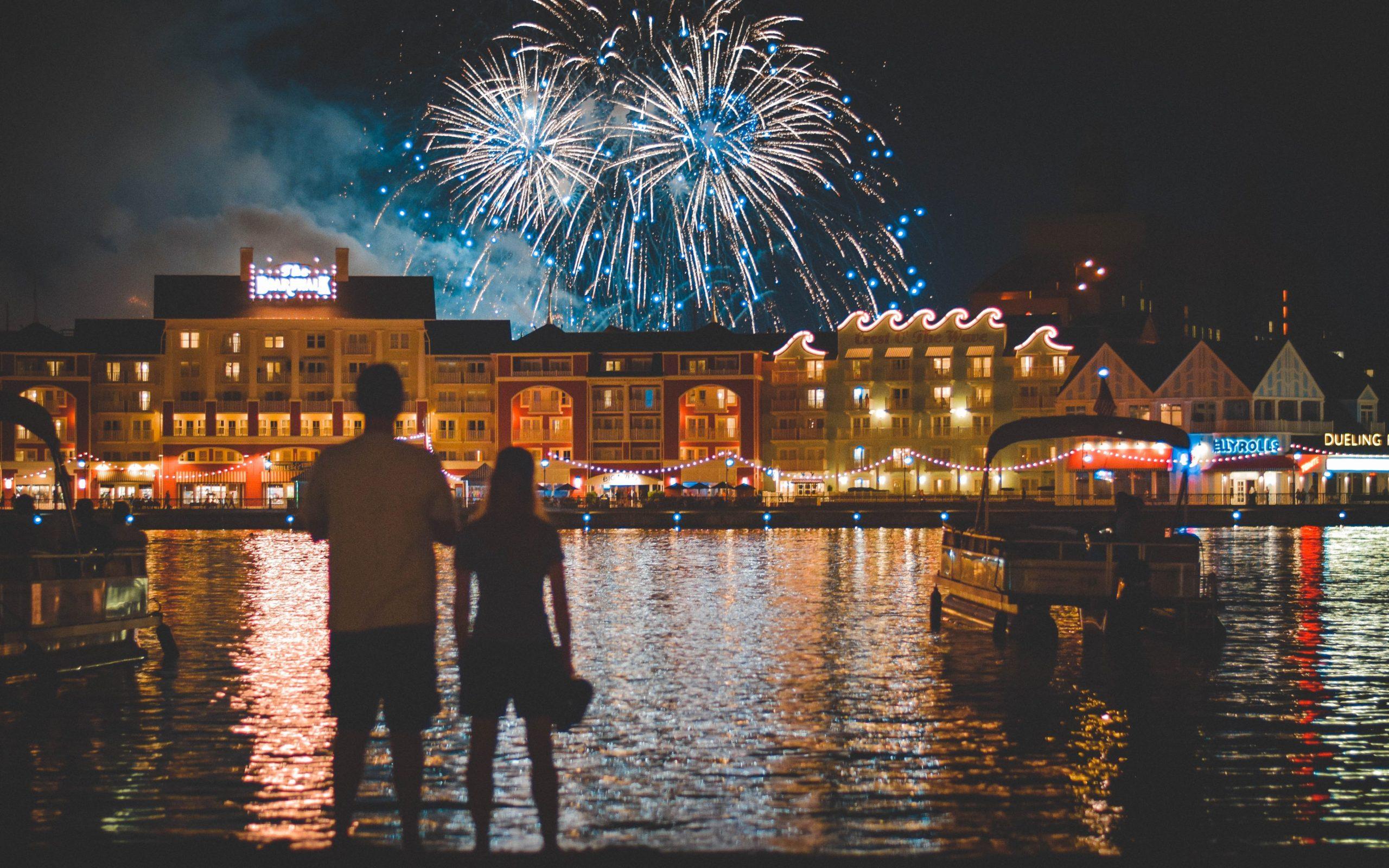 Man and woman watch fireworks above Disney's Boardwalk Resort