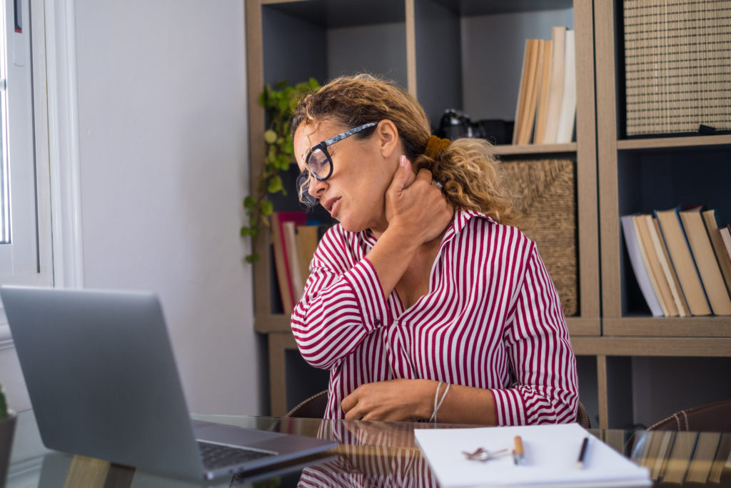 Photo of a woman sitting at a desk in her home office with a laptop. She appears to have neck pain and is holding her neck with her hand and closing her eyes.