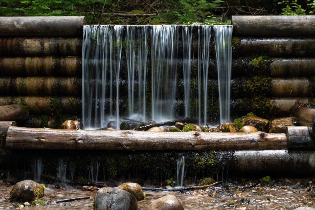 Waterfall over mossy logs in Oscoda, Michigan