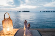 POV of person sitting on dock with their feet in front of them, relaxed, with a lantern, overlooking a large body of water and sky with clouds.