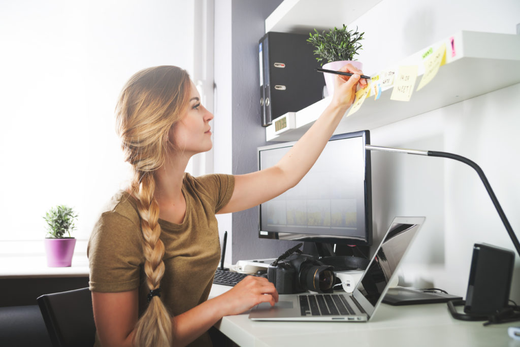 Woman working at desk and writing on sticky notes with a pen that are stuck to a shelf above her computer.