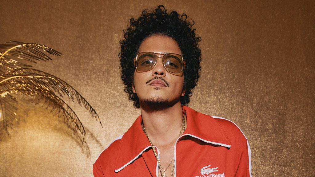 Pop star Bruno Mars rocks an afro, sunglasses, and an orange-red Lacoste zip up jacket with white trim as he poses for a photo in front of gold wallpaper and a gold brushed palm tree.