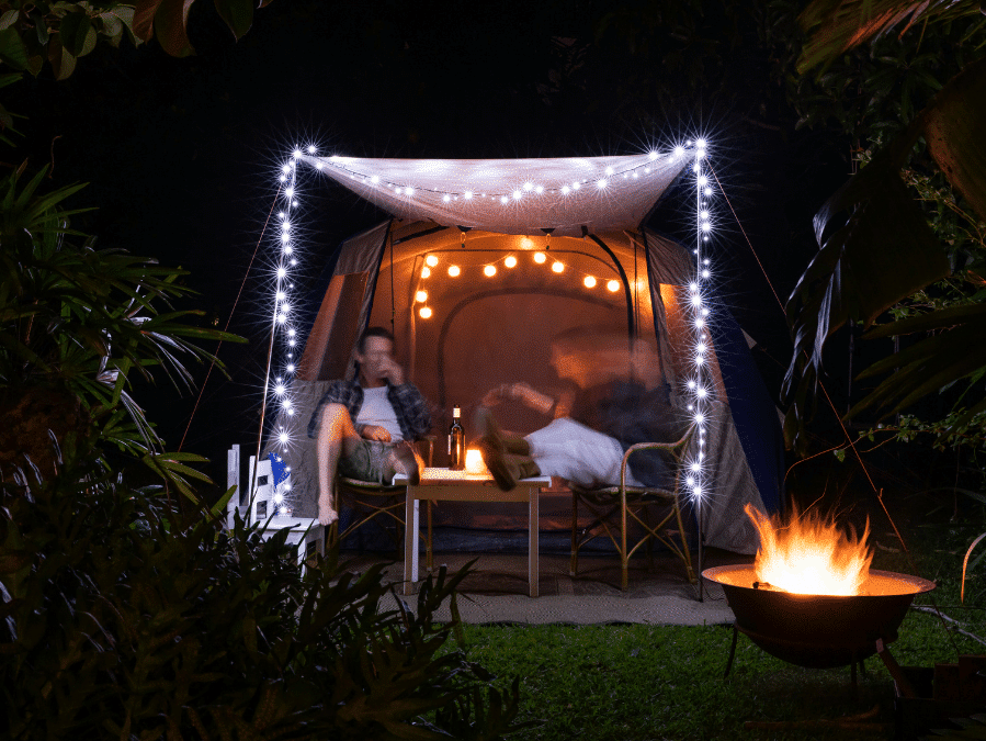 Couple sitting in tent in their backyard during staycation