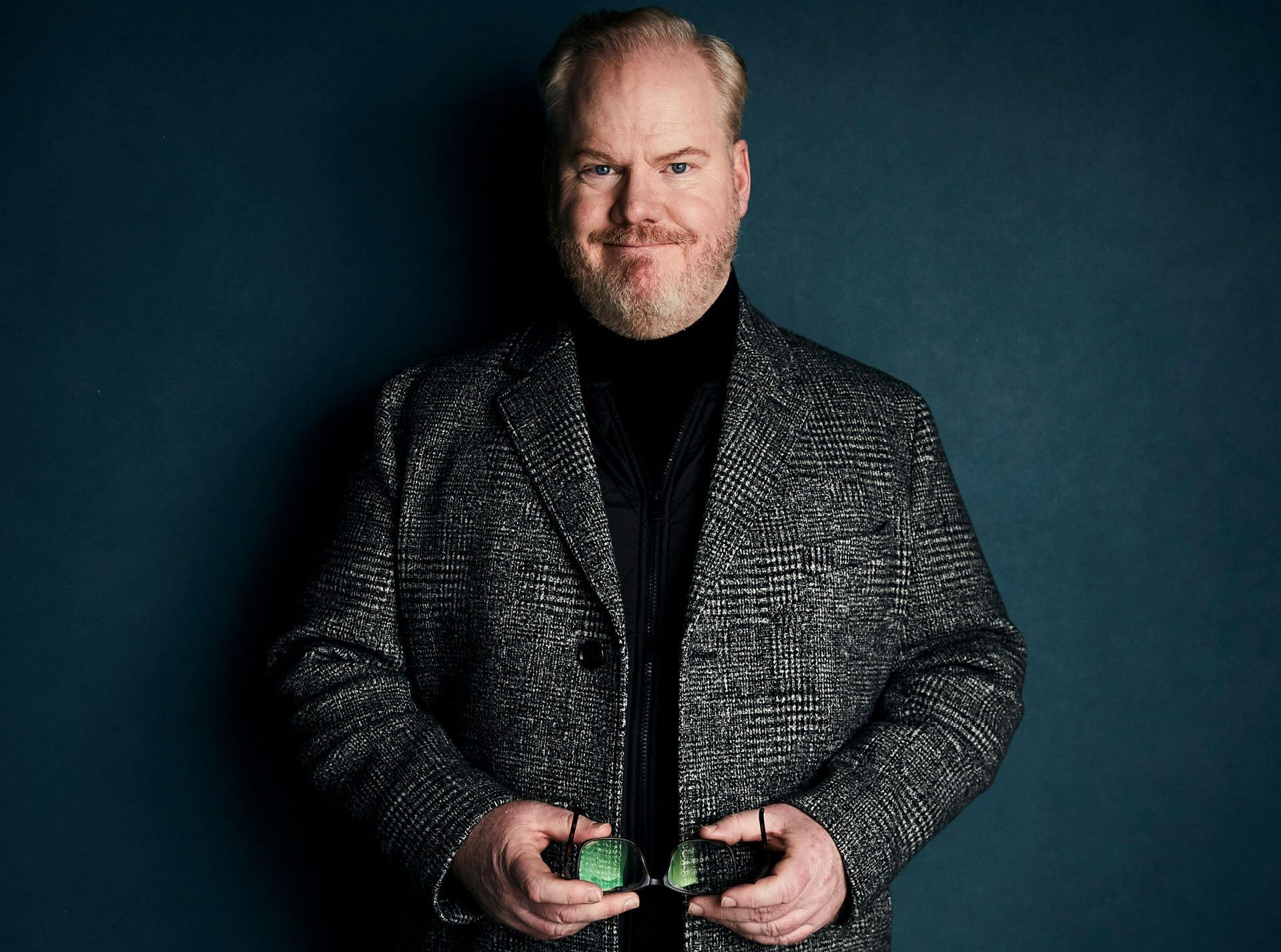 Comedian Jim Gaffigan wearing a plaid coat and black turtle neck poses in front of a dark blue background for a photo. Tickets available for August 2021 Las Vegas show.