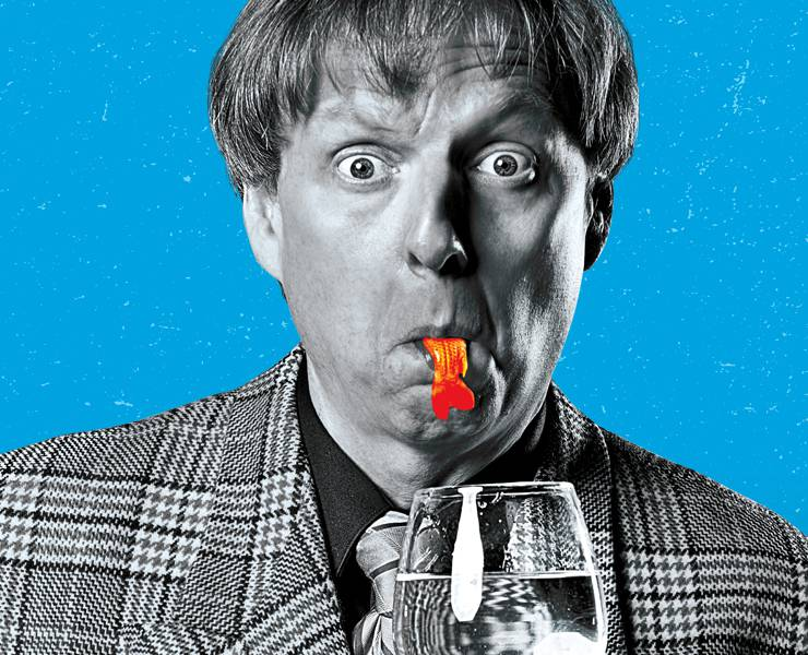 Comedian and magician Mac King in Black and White looking surprised with a goldfish in his mouth overlayed across a vibrant blue background.