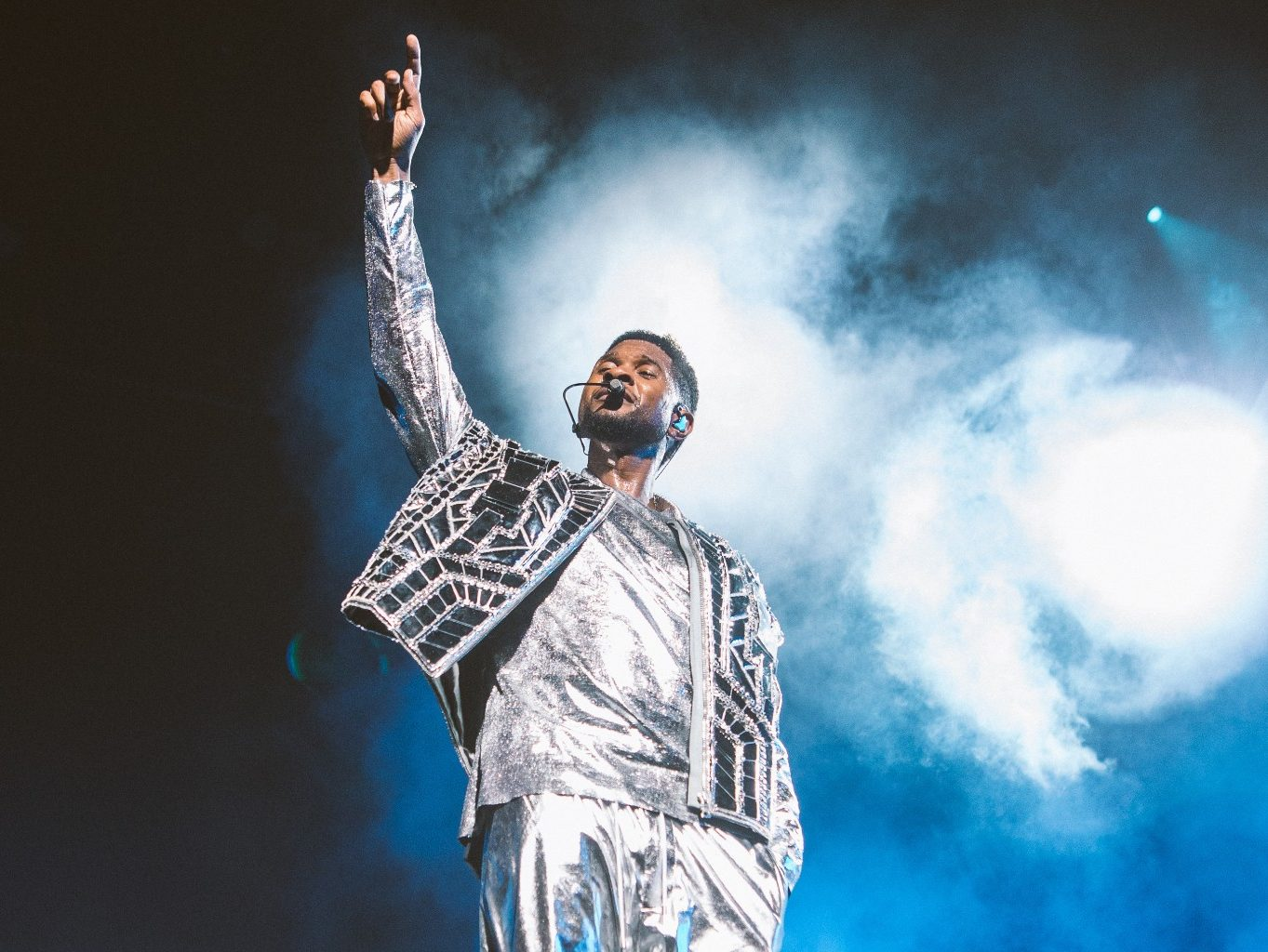Usher Raymond in silver clothes raising up one hand as he overlooks the crowd at his Las Vegas Residency at Caesar's Palace. Blue and black background with white fog.
