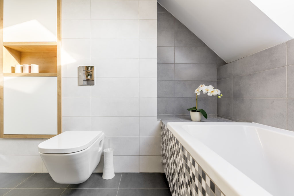 Bathroom in grey and white with bathtub and smart toilet, a bathroom design trends of 2021