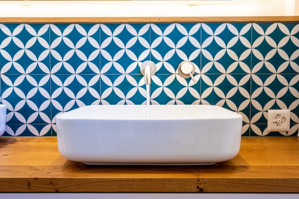 a trendy sink in front of a bold blue tile wall