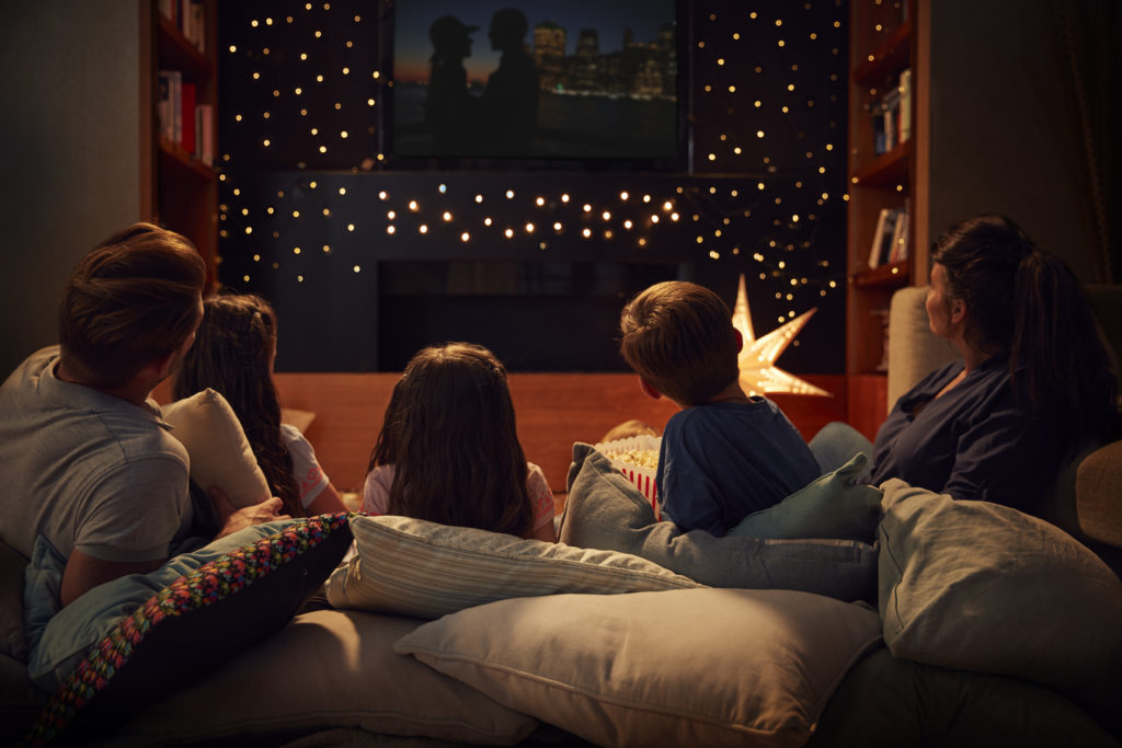 Family Enjoying Movie Night At Home Together during staycation