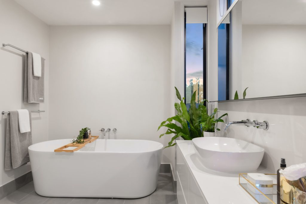 Photo of bathroom with deep soaking tub that fits cleanly in the space. Shows bathroom design trends.