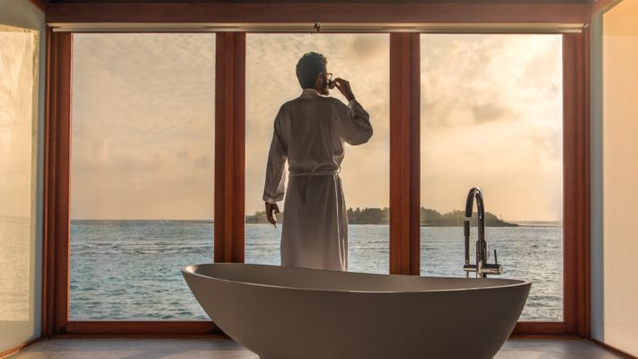 Man stands beside modern bathtub looking out the window at a body of water