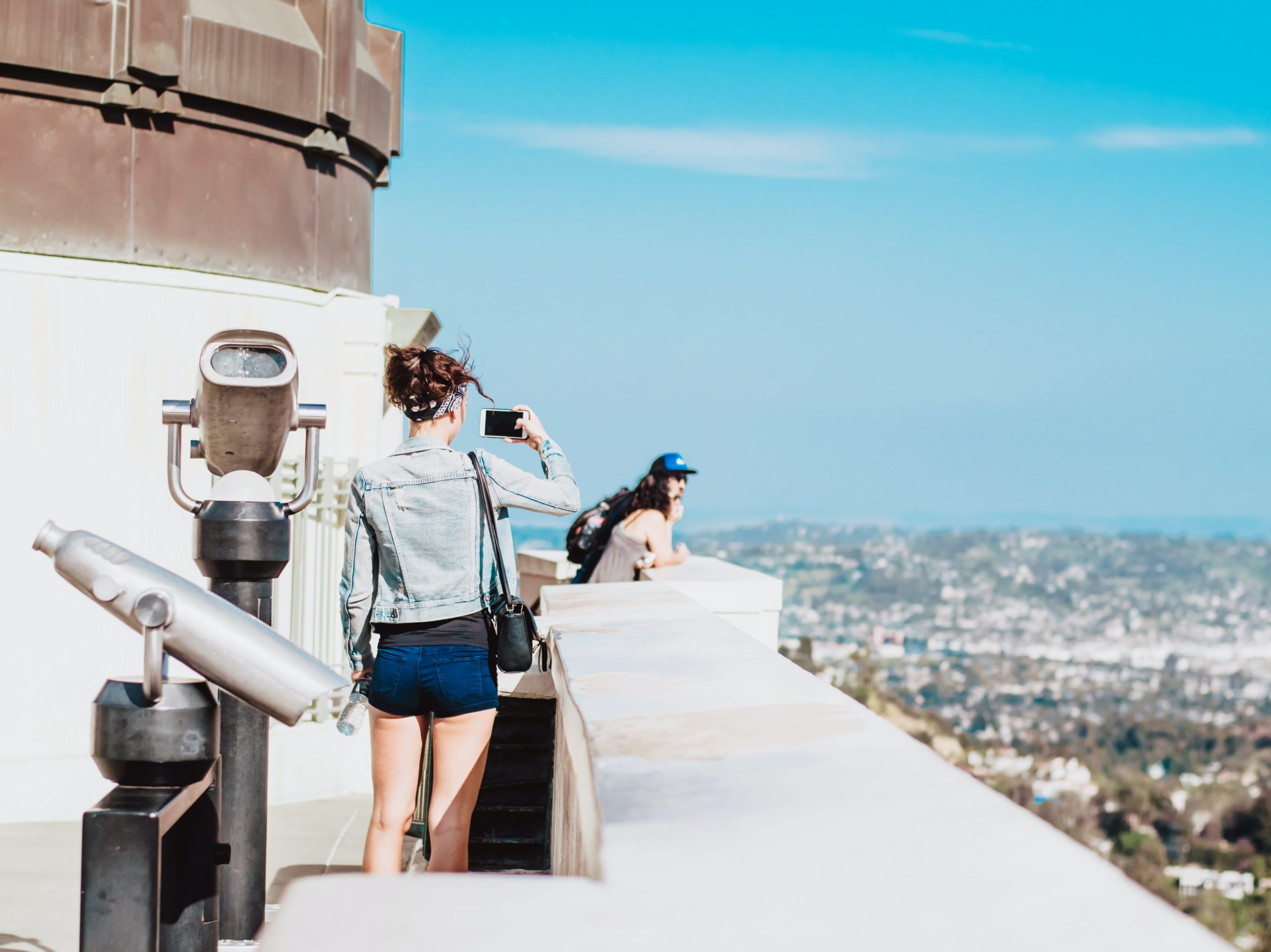 A girl takes a photo of the view from the top of the griffith observatory