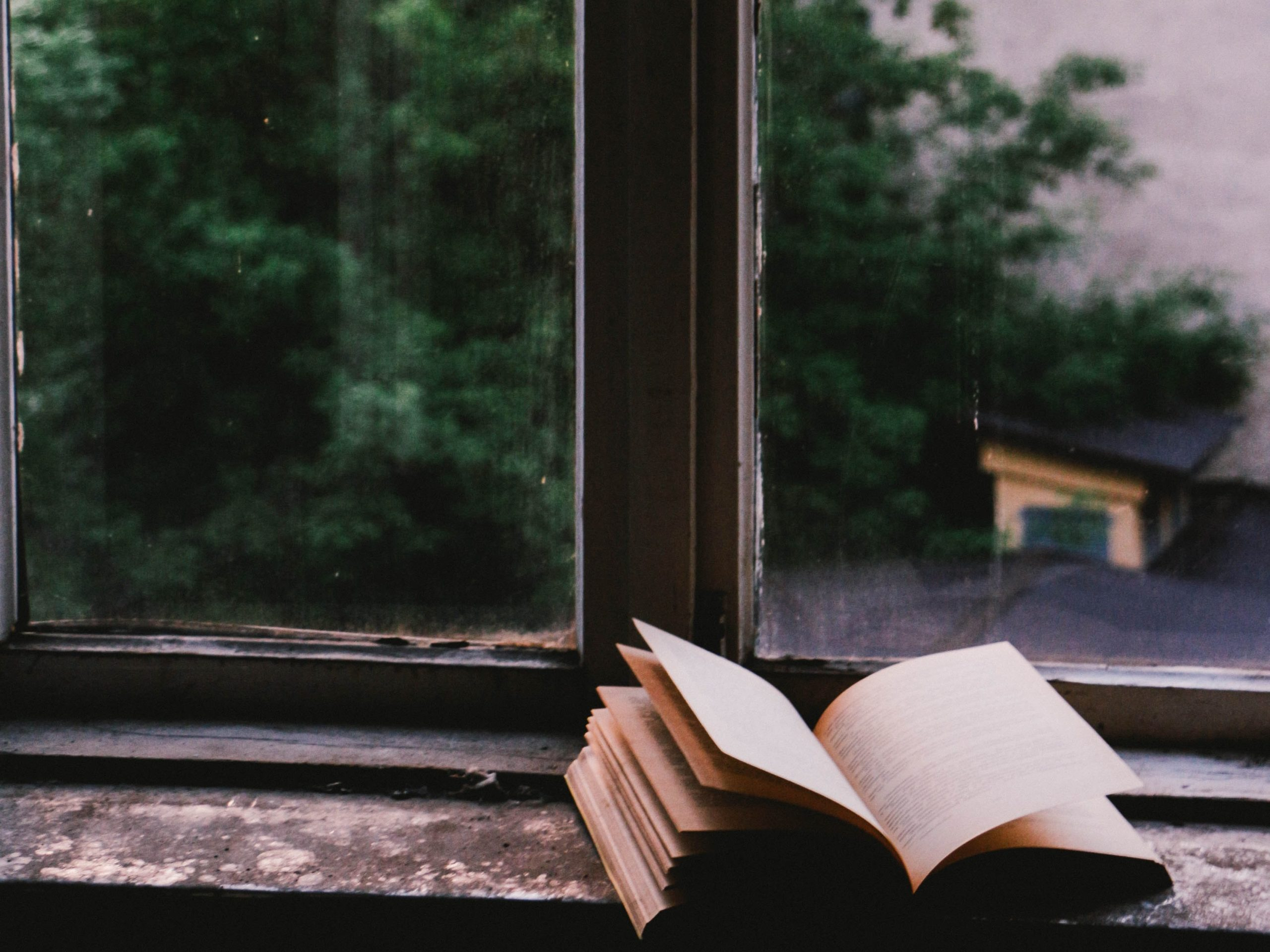 An old book is open on a window sill