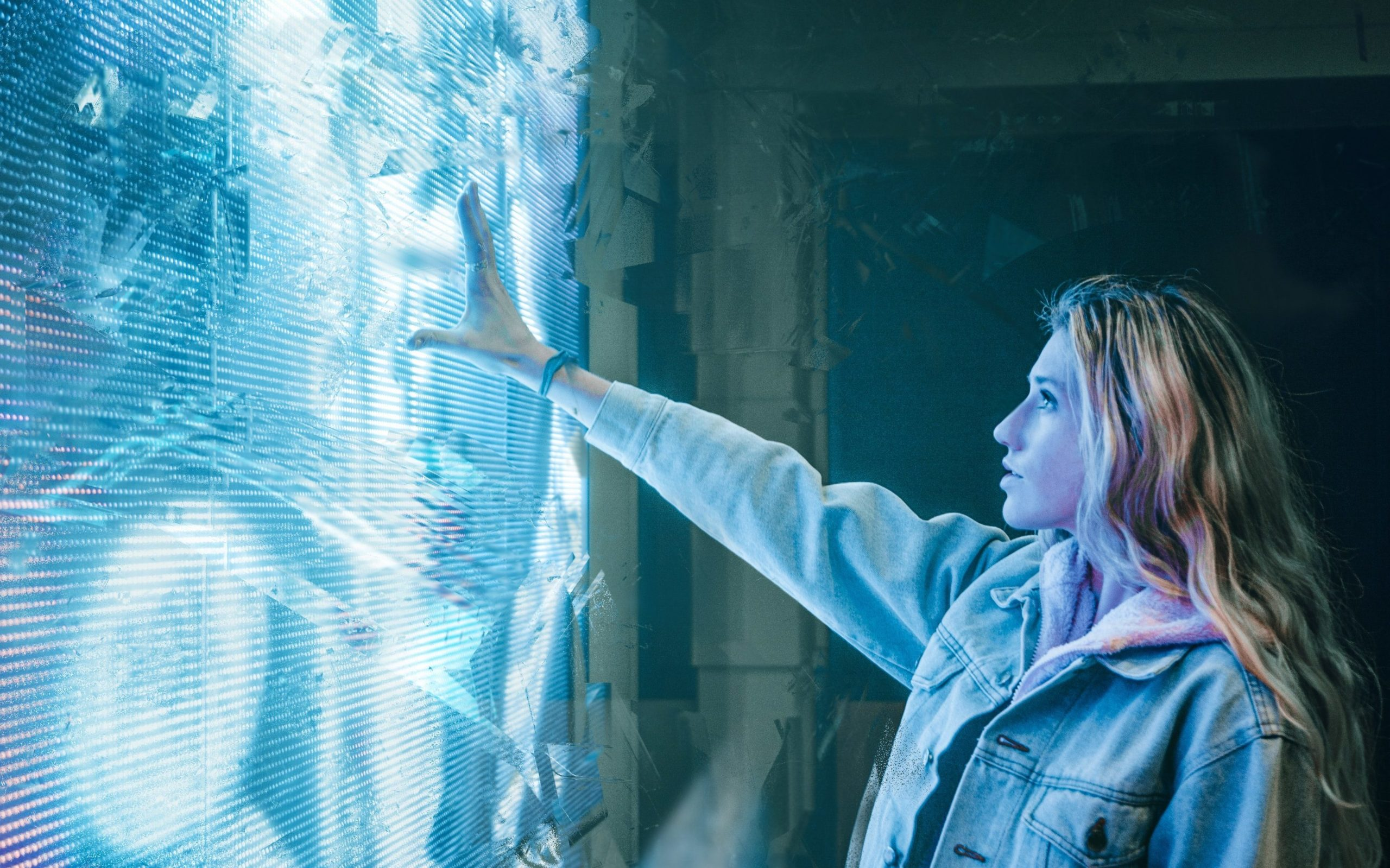 young woman touching a futuristic wall that is illuminated and blue and resembles a screen. smart home technology.