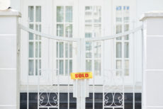 """Sign that says """"sold"""" on the gate of a large home"""
