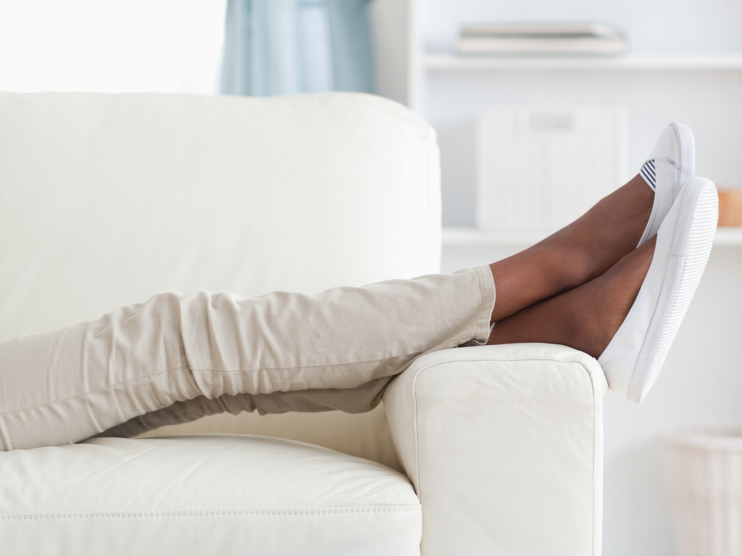 Young woman on couch putting her feet up during staycation