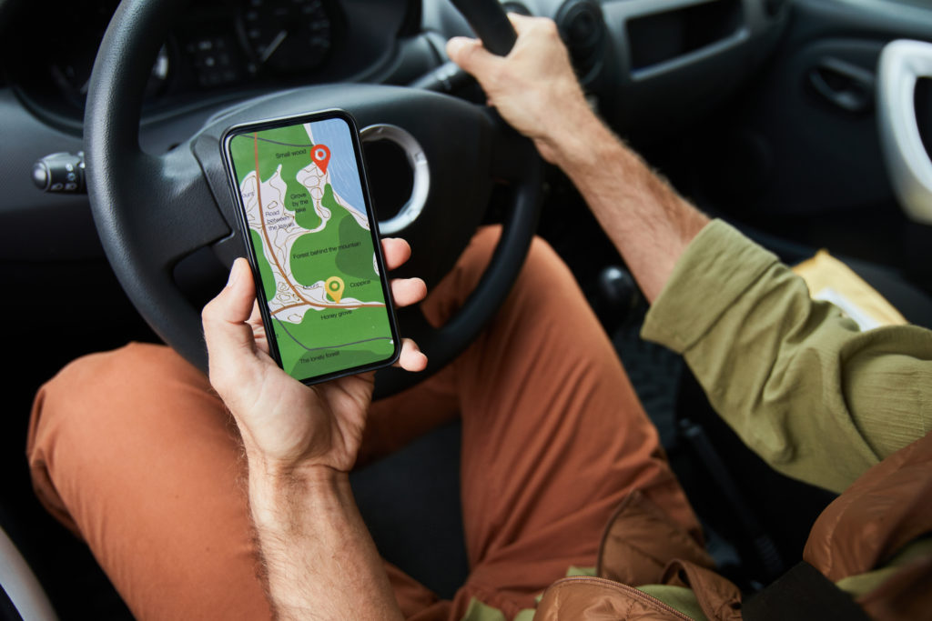 Close up of unrecognizable man driving car or van focus on hand holding smartphone with navigation app, copy space