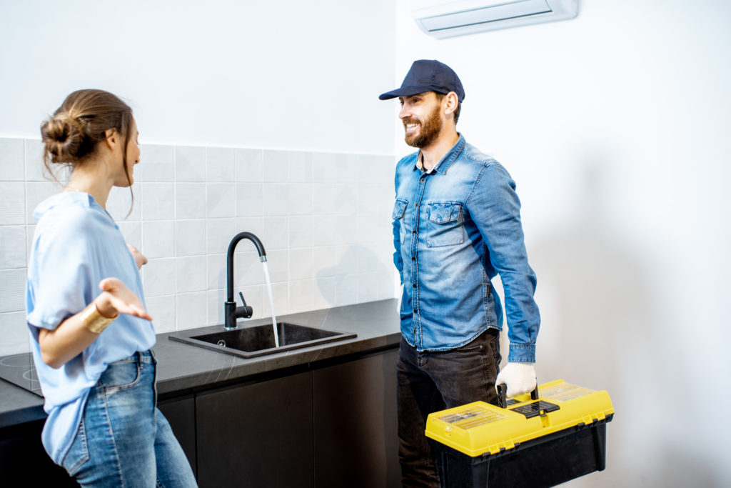 Handy man talking with young woman client after the repairment on the kitchen. Home repair service concept