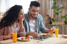 Joyful Middle-Eastern Couple Shopping Online With Digital Tablet While Having Breakfast In Kitchen, Young Arab Spouses Purchasing Grocery Delivery Or Browsing Internet While Enjoying Their Meal