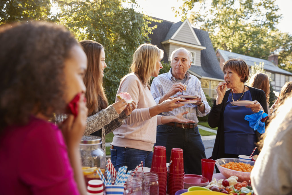 Neighbors talk and eat at a block party, close up