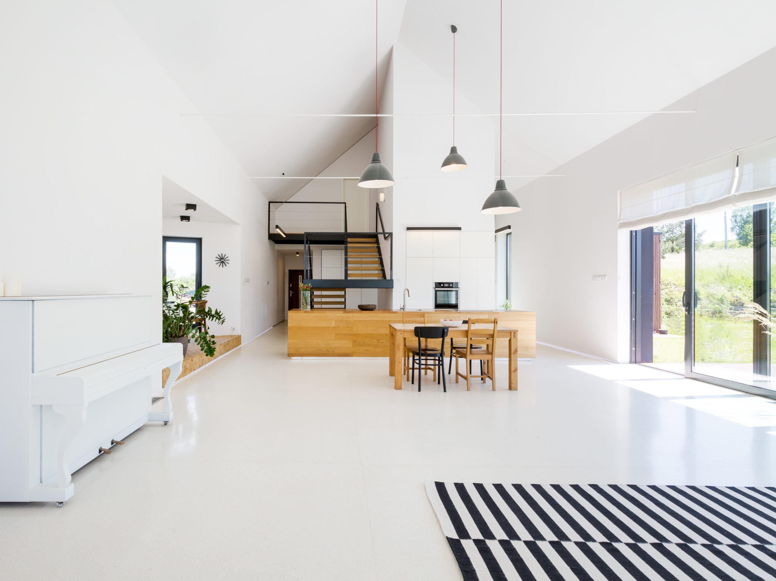Spacious Scandinavian style living room with white walls and striped carpet