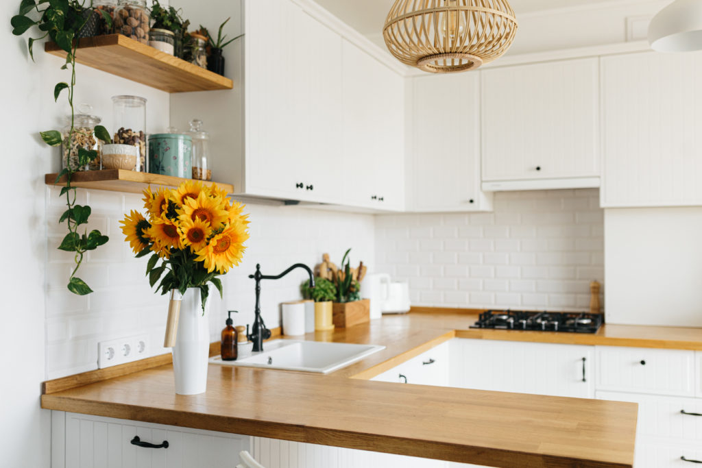 View on clean white simple modern kitchen in scandinavian style, kitchen details, wooden table, sunflowers bouquet in vase on the table