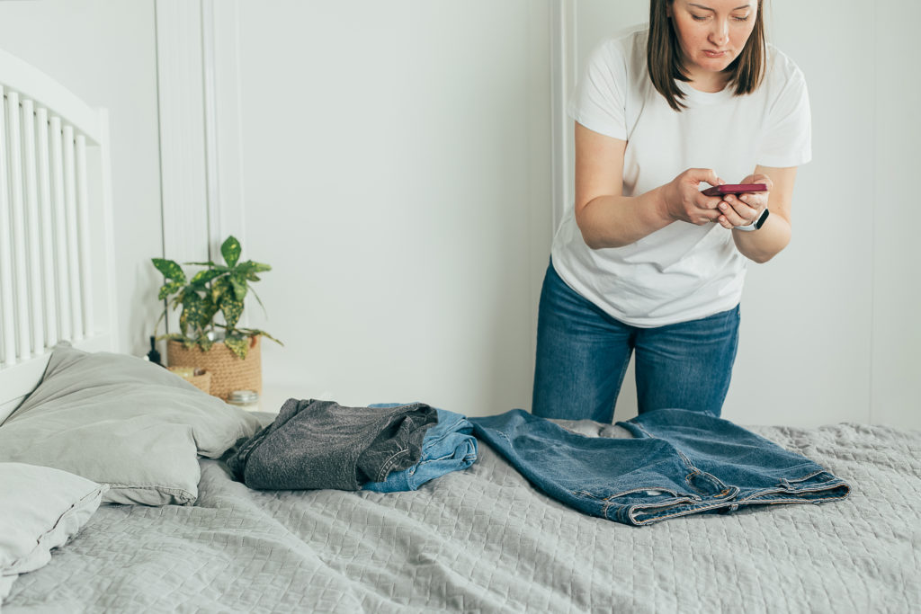 Woman taking photo of jeans on smartphone. Concept of secondhand, online sale, sustainability, sale of used