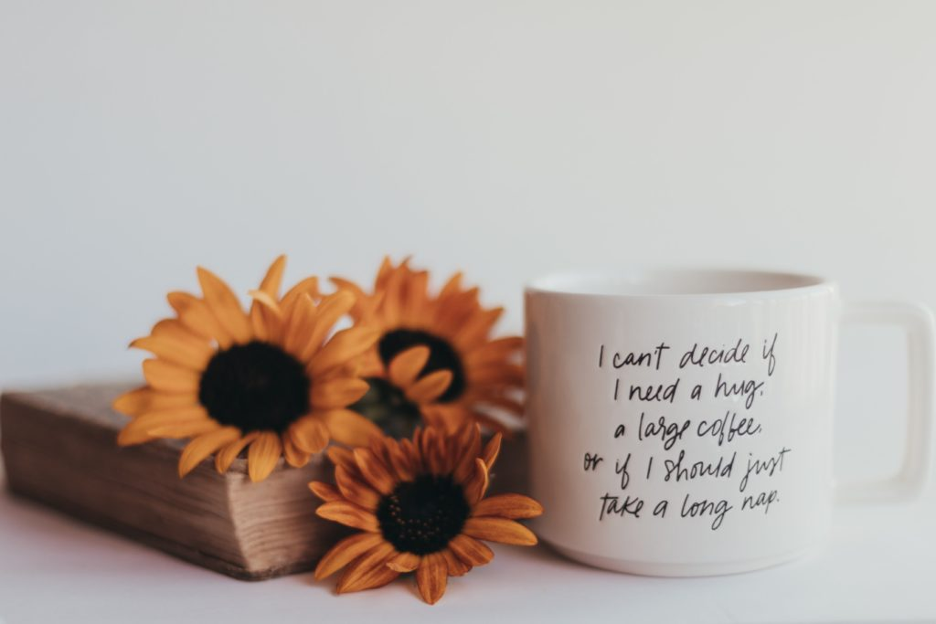 a coffee cup next to a book with sunflowers on it